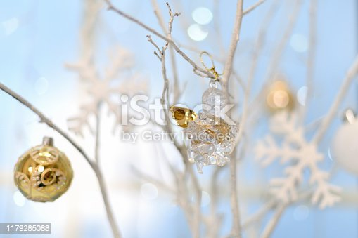 Christmas decoration. Transparent angel and Golden ball hanging on Christmas tree