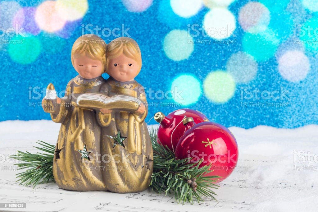 Christmas decoration with angel figure, red baubles, pine tree branches and musical score with a background composed of snow and shiny blue background stock photo