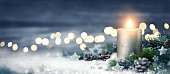 Christmas decoration with candle, lights, fir branches and ornaments on snow, panoramic format