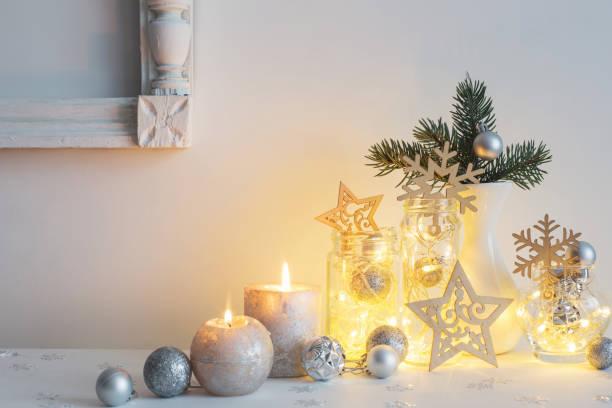 weihnachts-dekoration mit kerzen auf weiße hintergrundwand - weihnachten haus dekoration stock-fotos und bilder