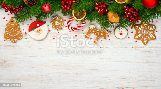 istock Christmas decoration with holiday tree branches, ball toys, gingerbread cookies 1044689944