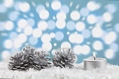 Christmas decoration with light bokeh in the background.Fir cones laying arround . Blue background.