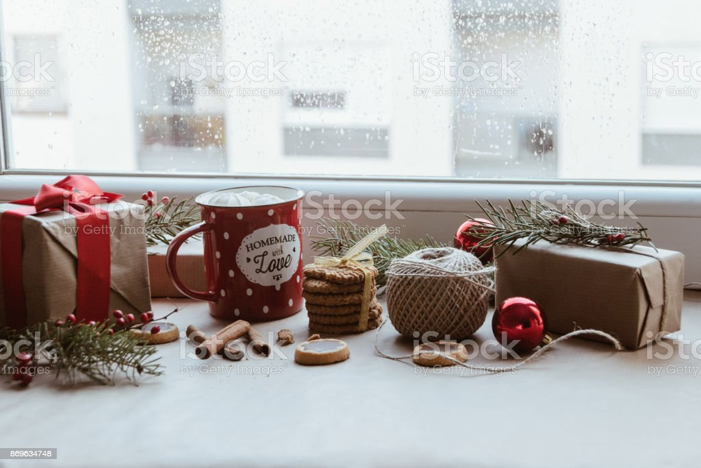 A Christmas decoration with a mug, Christmas presents, biscuits, and...