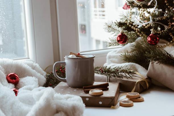 Christmas decoration with presents, mug, blanket, Christmas tree beside the window stock photo