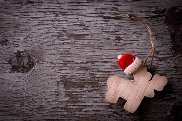 weihnachts-dekoration mit weihnachtsmütze auf hölzernen hintergrund mit textfreiraum - weihnachtsmannhüte aus erdbeeren stock-fotos und bilder