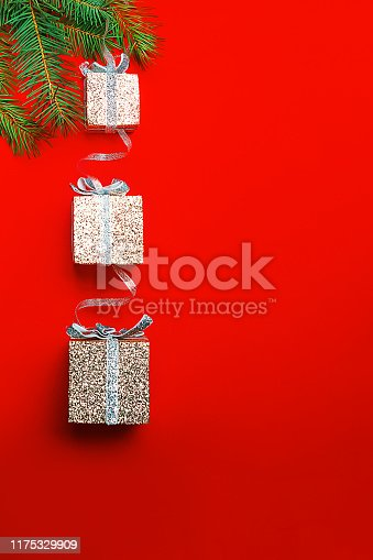 istock Christmas decoration with silver boxes as gift on branch fir tree on red background. 1175329909
