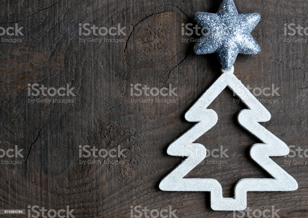 Christmas decoration.Decorative white fir tree with silver star on old wooden background.Winter holidays,Merry Christmas concept. stock photo