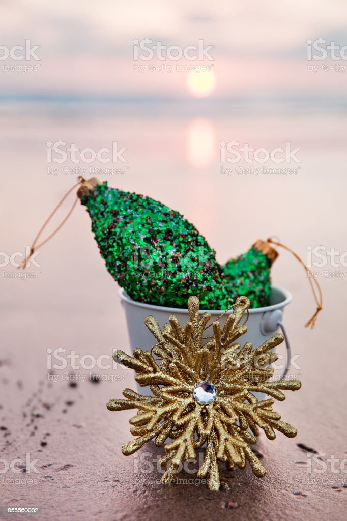 Christmas Decorations collected in a white bucket with Golden Snowflake at sunset stock photo