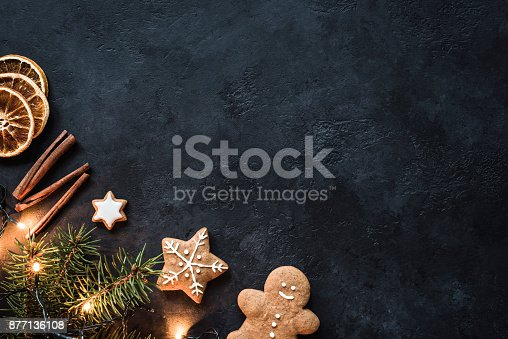 istock Christmas Decorations, Gingerbread cookies, Christmas lights and Spices on dark background. Design mock up 877136108