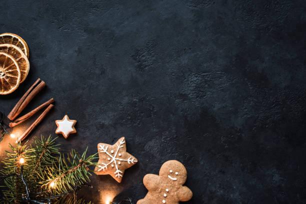 christbaumschmuck, lebkuchen, weihnachtsbeleuchtung und gewürzen auf dunklem hintergrund. mock-up design - holzdeko weihnachten stock-fotos und bilder