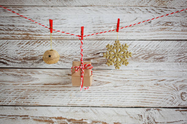 christmas decorations hanging on cord on white wooden background. - christmaas imagens e fotografias de stock