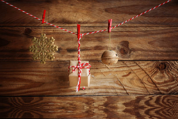 christmas decorations hanging on cord on wooden background. - christmaas imagens e fotografias de stock