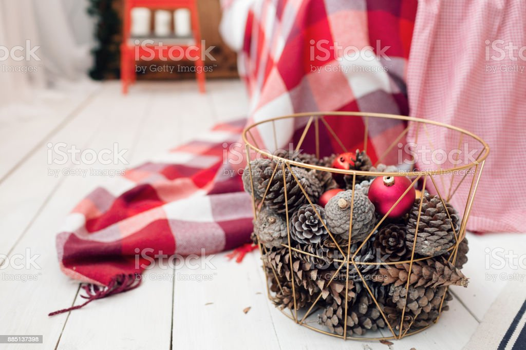 christmas decorations in basket and pine cones on floor close up royalty free stock