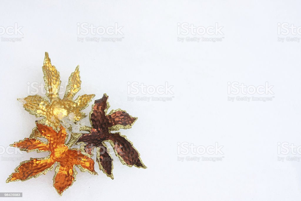 Christmas decorations in the shape of leaves on snow royalty-free stock photo