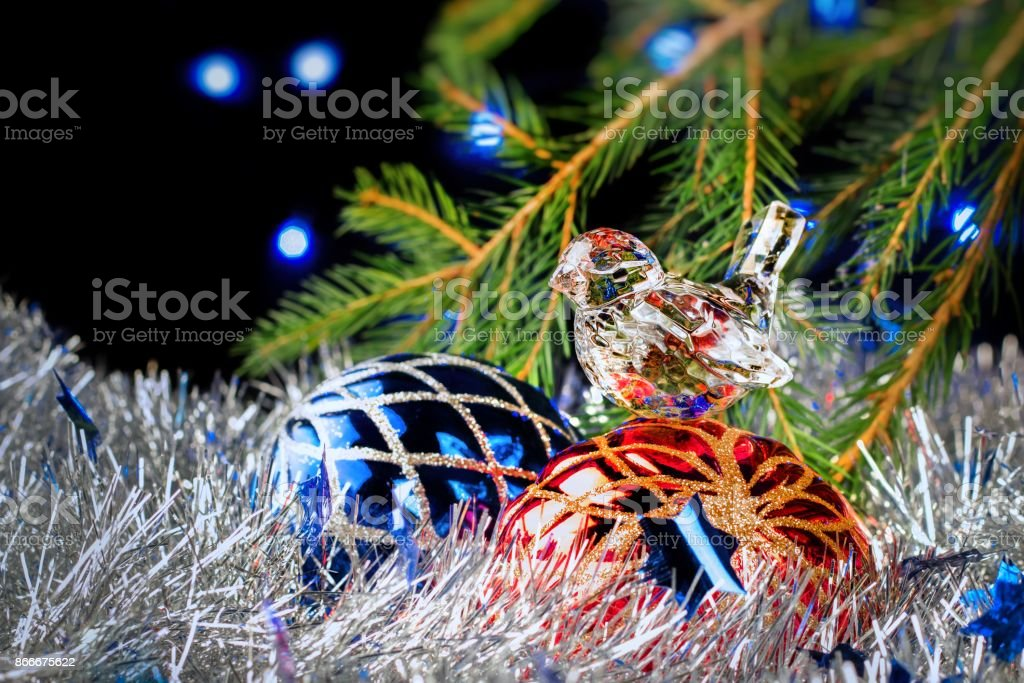 christmas decorations lying in tinsel and fir branches on a dark background with blurred lights royalty