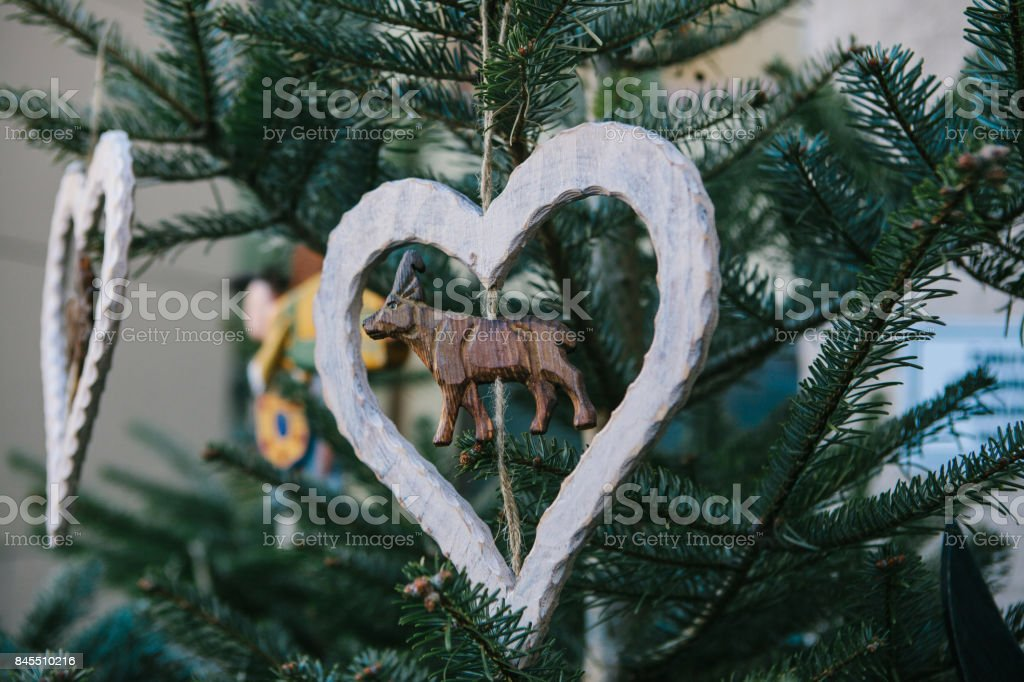 christmas decorations on a christmas tree in the form of a wooden deer inside the heart