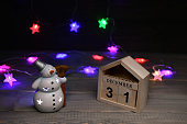 Christmas decorations on a wooden background: wooden cubes with the numbers December 31, glowing snowman,  with a multicolored garland in the background. Selective focus