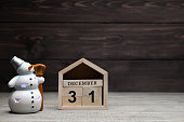 Christmas decorations on a wooden background: wooden cubes with the numbers December 31 and a glowing snowman. Selective focus