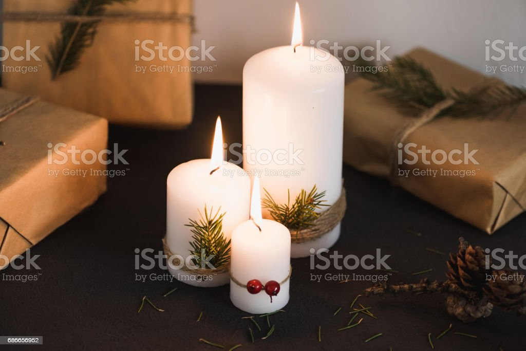 Christmas decorations on tha table, lit candles and gifts Lizenzfreies stock-foto