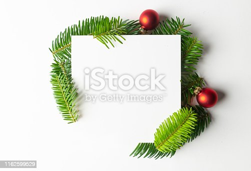 Christmas decorations with empty card on white background.