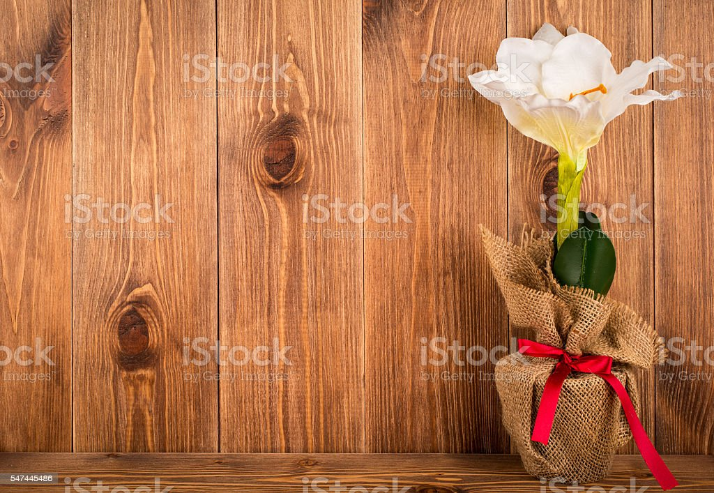Christmas decorative artificial white amaryllis flower on wooden background.. stock photo