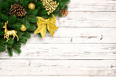 istock Christmas decorative background border with red and gold bauble decorations, gold star, deer, christmas tree toy, spruce pine, pine cones, fir branches on white wood rustic with copy space. Top view 1071660910