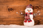 Christmas decorative snowman on brown wooden background.
