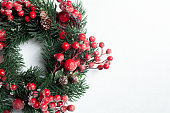 istock Christmas decorative wreath of holly, ivy, mistletoe, cedar and leyland leaf sprigs with red berries over white background. 1072564918