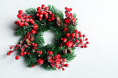istock Christmas decorative wreath of holly, ivy, mistletoe, cedar and leyland leaf sprigs with red berries over white background. 1072564928
