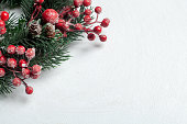 istock Christmas decorative wreath of holly, ivy, mistletoe, cedar and leyland leaf sprigs with red berries over white background. 1072564934