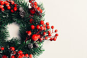 istock Christmas decorative wreath of holly, ivy, mistletoe, cedar and leyland leaf sprigs with red berries over white background. 1078776908
