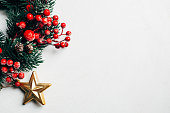 istock Christmas decorative wreath of holly, ivy, mistletoe, cedar and leyland leaf sprigs with red berries over white background. 1078776916