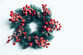 istock Christmas decorative wreath of holly, ivy, mistletoe, cedar and leyland leaf sprigs with red berries over white background. 1078776924