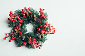 istock Christmas decorative wreath of holly, ivy, mistletoe, cedar and leyland leaf sprigs with red berries over white background. 1083334502