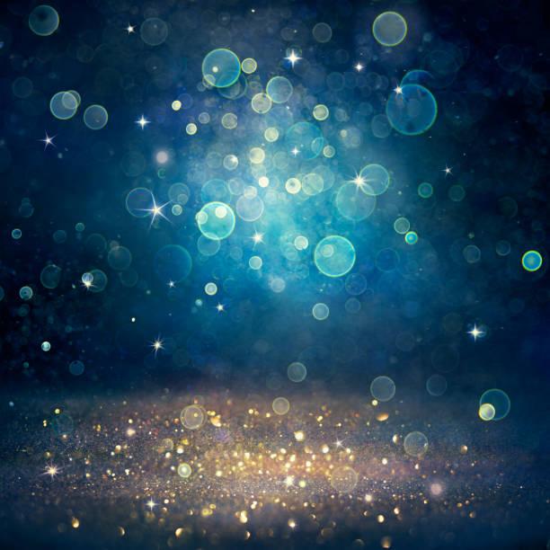 christmas defocused - poussière de paillettes d'or sur le fond bleu - festivité photos et images de collection