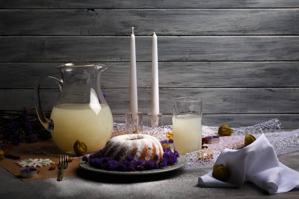 un dessert de noël avec glaçage et une cruche de grosse pleine de boissons fruitées sur fond gris en bois. objets de décoration. - année du mouton photos et images de collection