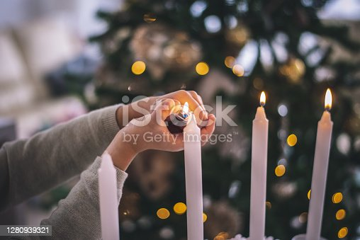 Christmas detail, lightning candles. Kid enjoy in living room during Christmas Celebration, Cheerful Christmas time