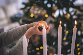 istock Christmas detail, lightning candles. Kid enjoy in living room during Christmas Celebration, Cheerful Christmas time 1280939321