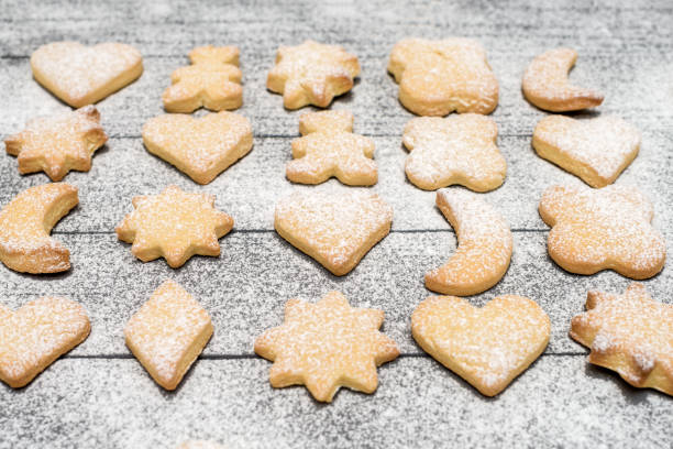Christmas different shaped cookies with sugar powder on wooden table Christmas different shaped cookies with sugar powder on wooden table. Top view cookie cutter stock pictures, royalty-free photos & images