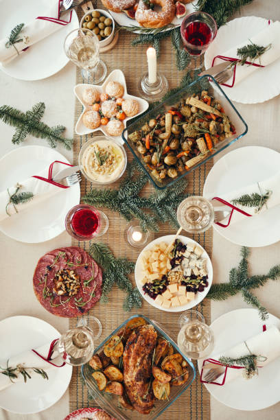 Christmas Dinner Table Top View Top view background of beautiful dinner table decorated with fir branches set for Christmas banquet, copy space table top view stock pictures, royalty-free photos & images