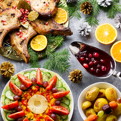 istock Christmas dinner with roasted meat steak, Christmas Wreath salad, baked potato, grilled vegetables, cranberry sauce. 1083266582