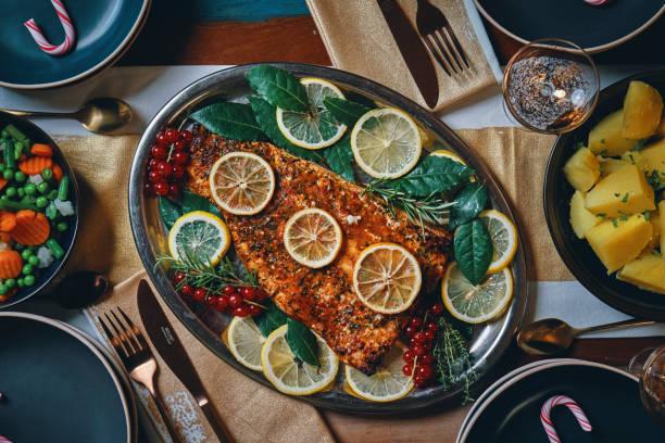 weihnachtsessen mit lachs fischfilet, gemüse, polenta und weihnachtskuchen - lachs meeresfrüchte stock-fotos und bilder