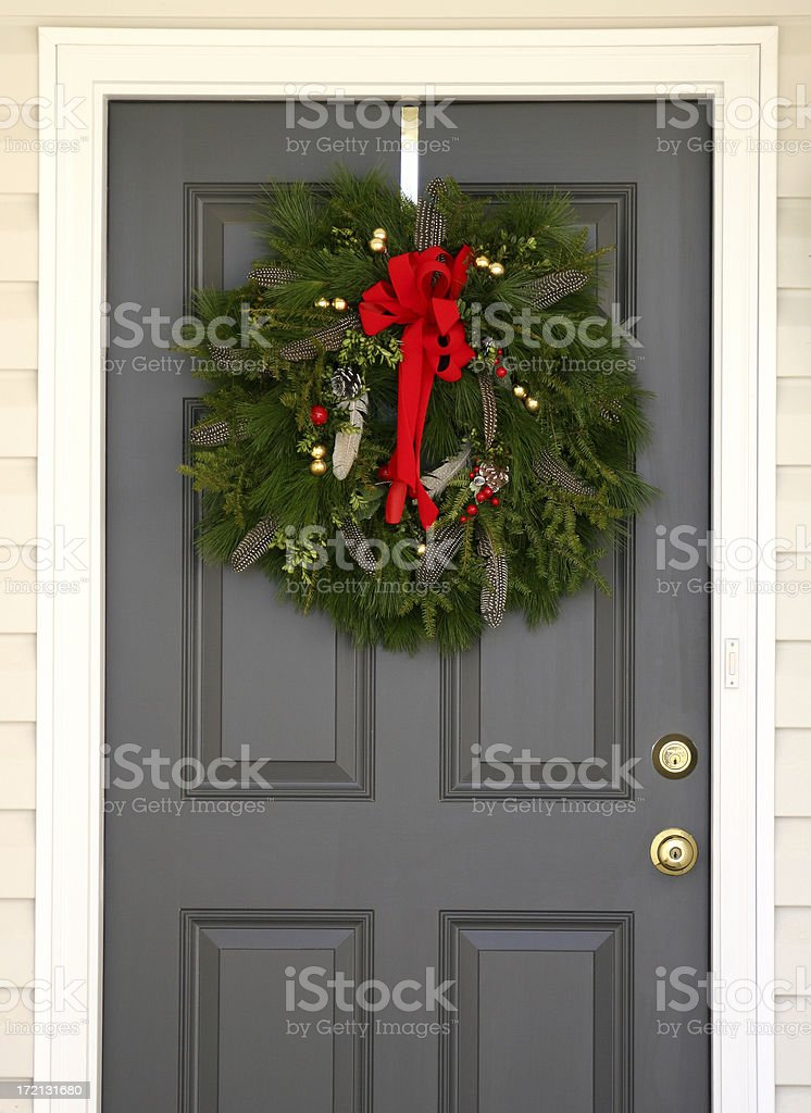 a gray door decorated with a Christmas wreath.