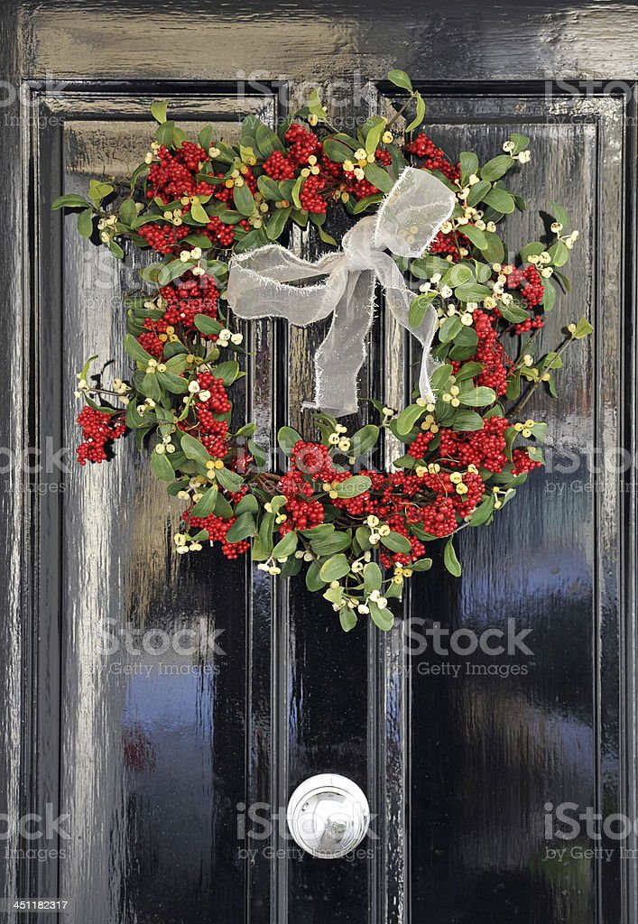 Colourful yule wreath with mistletoe and holly decorates a period...