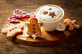 Christmas drink. Cup of cappuccino coffee with stars drawing and gingerbread cookie on wooden board