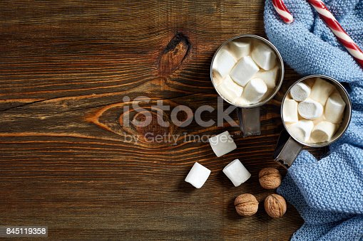 istock Christmas drink. Mug hot coffee with marshmallow, red candy cane on the wooden background. New Year 845119358