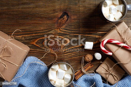 istock Christmas drink. Mug hot coffee with marshmallow, red candy cane on the wooden background. New Year 845942756