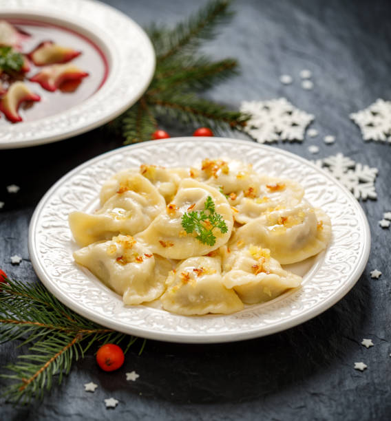 weihnachten teigtaschen gefüllt mit champignons und kohl auf einem weißen teller auf einem dunklen hintergrund. - knödel kochen stock-fotos und bilder