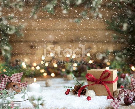 Christmas eco friendly gift box lying in snow on an old wooden background with dreamy glittery lights