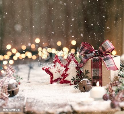 Christmas eco friendly star and tree ornaments and a gift box on an old wood background with defocused lights and falling snow